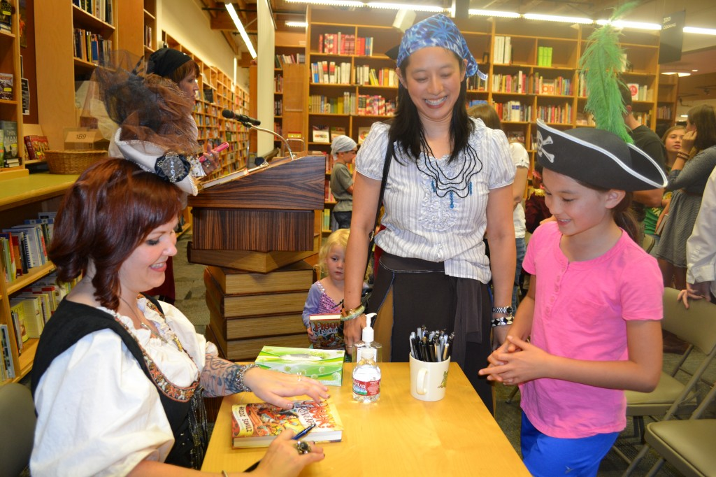 Signing a book for author Fonda Lee and her daughter Photo by Kelly Garrett